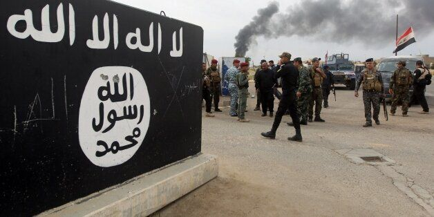 Iraqi security forces and Shiite fighters from the Popular Mobilisation units gather next to a mural depicting the emblem of