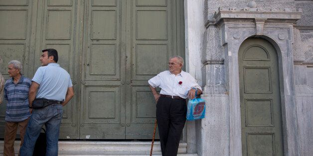 Pensioners stand outside the main gate of the national bank of Greece as they wait to withdraw a maximum of 120 euros ($134)