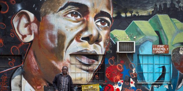 FILE - In this Wednesday, July 22, 2015 file photo, a man walks away after leaning his bicycle against a mural of President B