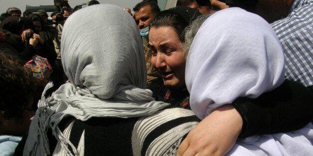 Yazidi women, released by Islamic State group militants, hug as they arrive in Kirkuk, 180 miles (290 kilometers) north of Ba