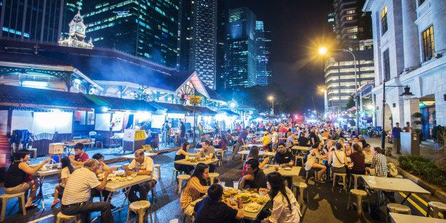 Diners sit at restaurant tables at the Lau Pa Sat food court as commercial buildings stand illuminated at night in the centra