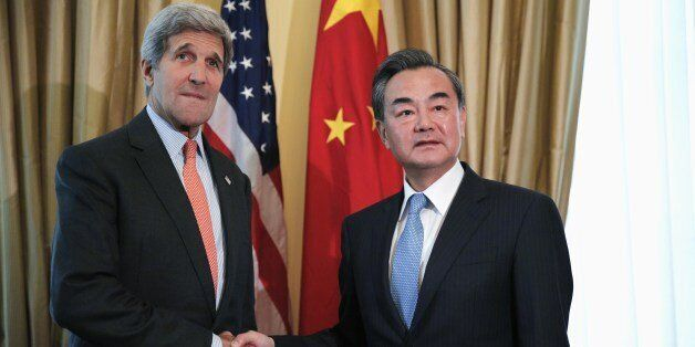 US Secretary of State John Kerry (L) shakes hands with Chinese Foreign Minister Wang Yi at a hotel where the Iran nuclear tal
