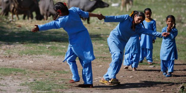 Young Indian children play before classes begin at their government-run school on the outskirts of Jammu, India, Thursday, Ap