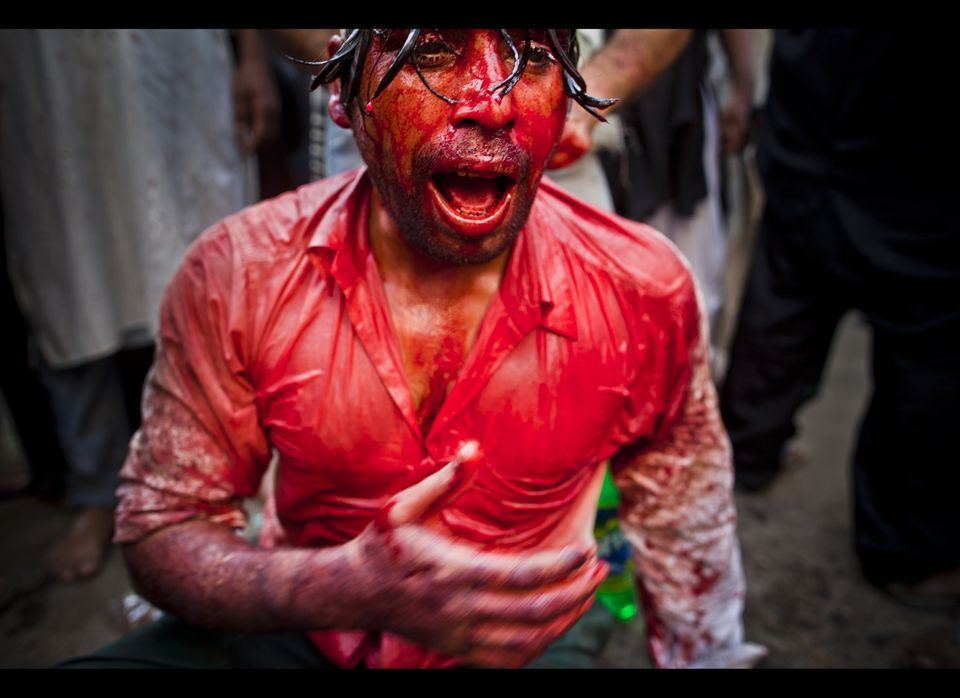 A Shiite Muslim beats his chest as part of a self-flagelation ritual during a religious procession of the Ashura mourning per