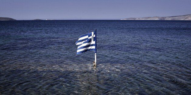 This photo taken on July 29, 2015 shows a Greek flag floating in the sea at the Kalamitsa beach on Skyros island. Greece expe