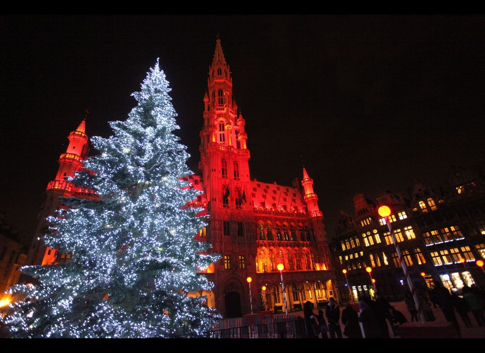 Twinkling blue lights illuminate a tree in front of Brussels' Town Hall at La Grande Place.