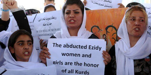 Iraqi Yazidi women hold placards during a protest outside the United Nations (UN) office in the Iraqi city of Arbil, the capi