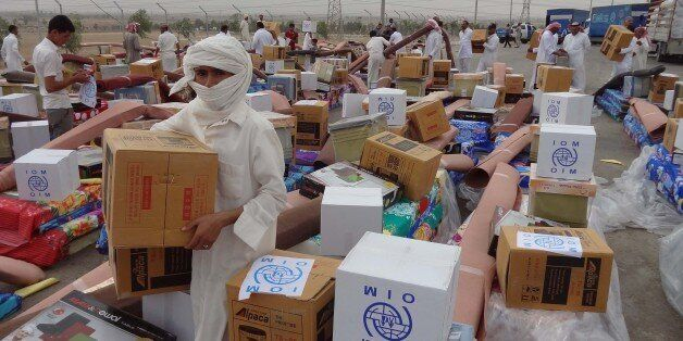 Iraqi men collect humanitarian aid supplies provided by the US development agency USAID to displaced Iraqis who have fled cla