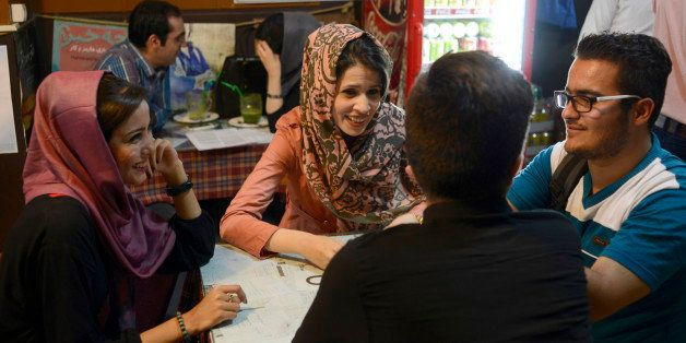 TEHRAN, IRAN - MAY 10, 2015: Iranian youth socialize while sat in a coffeeshop located near the university on Revolution Stre