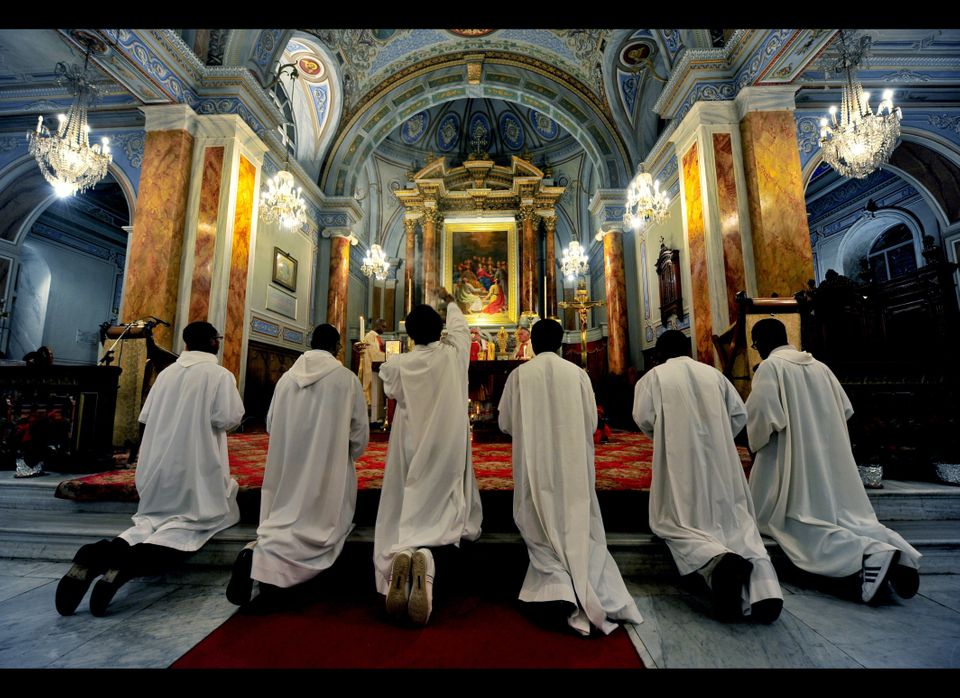 Catholic priests pray at the St. Esprit Church during the Christmas mass at midnight, in Harbiye, downtown Istanbul on Decemb
