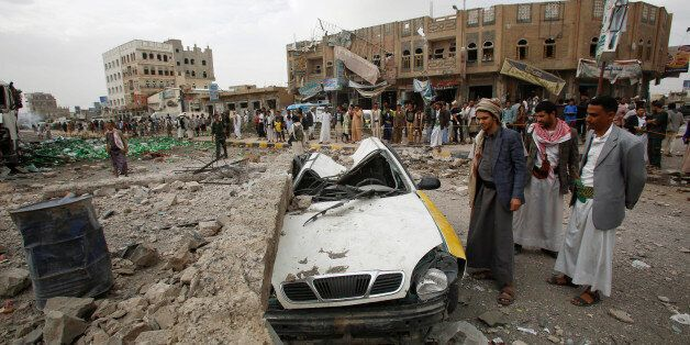 FILE - In this July 14, 2015, file photo, people stand next to a vehicle destroyed following airstrikes by the Saudi-led coal