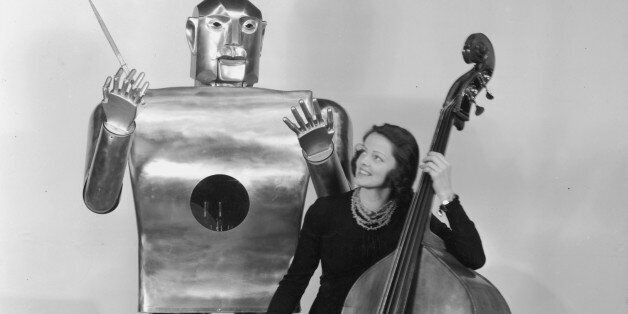 circa 1939:  Musician Lois Kendall plays the cello while a mechanical man named Elektro 'conducts' on stage as part of a West