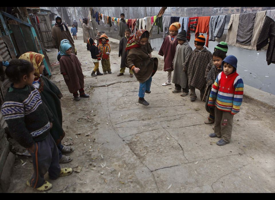 Kashmiri Muslim children play hopscotch outside their house on a cold day in Srinagar.