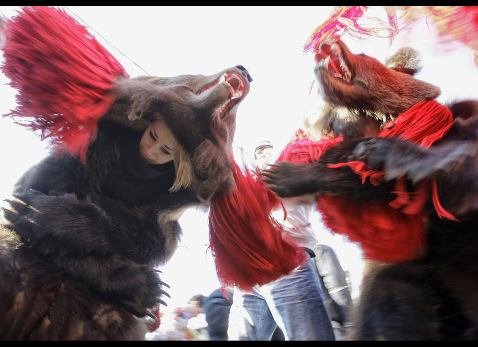 Children wearing  bear furs are seen during New Year ritual dances attended by hundreds in Comanesti, northern Romania.