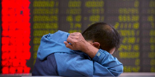 A Chinese investor monitors stock prices at a brokerage house in Beijing, Tuesday, Aug. 25, 2015.  China's main stock market