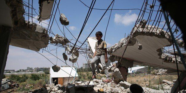 A Palestinian boy plays in the rubble of houses destroyed during the 50-day war between Israel and Hamas militants in the sum