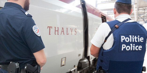 Member of belgian and french police stay next to a Thalys train at the Brussels Midi - Zuid train station, on Saturday, Aug.
