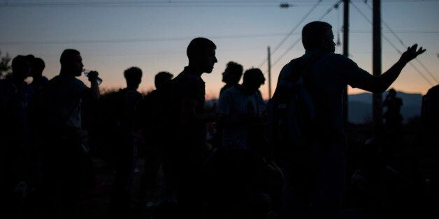 Syrian refugees wait at the border railway station of Idomeni, northern Greece, in order to be allowed...
