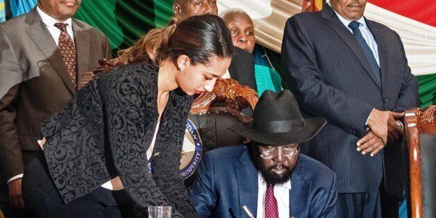 South Sudan's President Salva Kiir (C) signs a peace agreement in the capital Juba, on August 26, 2015. The deal is designed