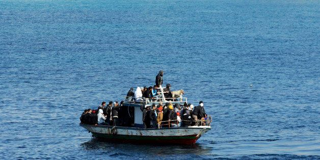 A boatload of would-be migrants believed to be from North Africa is seen moments before being rescued by the Italian Coast Gu