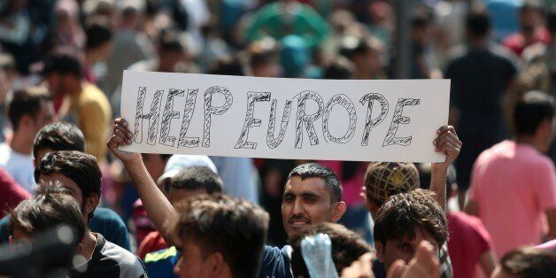 A man hold a placard reading 'Help Europe' as Syrian and Afgan refugees attend a protest rally to demand to travel to Germany