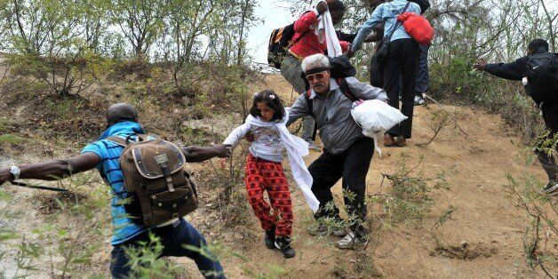 Migrants and refugees cross from Greece into Macedonian near the village of Idomeni, in northern Greece on September 8, 2015.