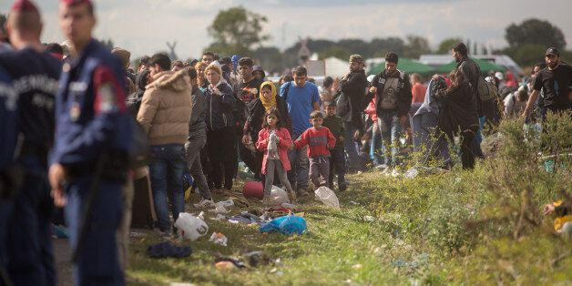 BUDAPEST, HUNGARY - SEPTEMBER 07:  Migrants who have just crossed into Hungary wait for buses to take them to a reception cam