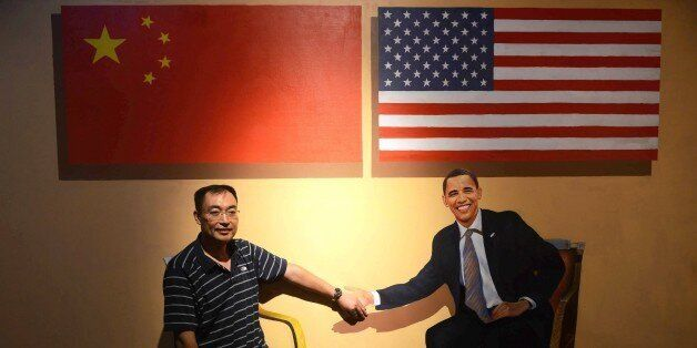 This photo taken on August 23, 2015 shows a visitor posing with a perspective painting of US President Barack Obama at the 4D