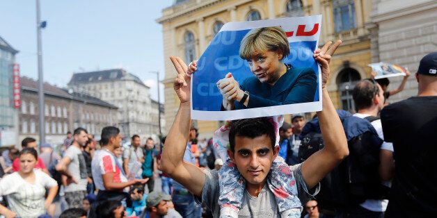 A man holds up a poster of German Chacellor Angela Merkel before starting a march out of  Budapest, Hungary, Friday, Sept. 4,