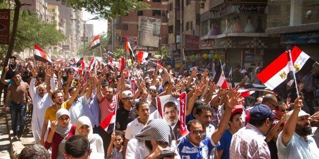 Members of the Muslim Brotherhood hold up pictures of their ousted President Mohammed Morsi during a protest two years after