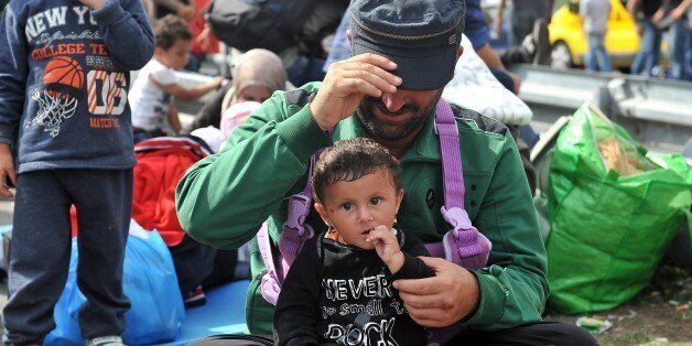 A man holds a baby girl as migrants and refugees sit on the asphalt at the official border crossing between Serbia and Hungar