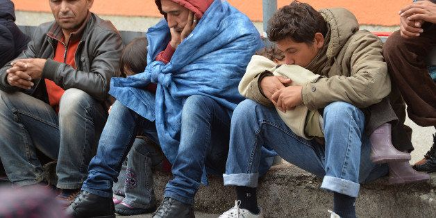 Migrants sit on a platform at the rail station in Freilassing, Germany, Monday, Sept. 14, 2015, after they have been taken of