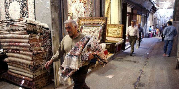 In this Monday, Aug. 10, 2015 photo, an Iranian man carries a carpet through Tehran's old, main bazaar, Iran. Iran's famed ca