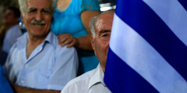 An elderly supporter of New Democracy party holds a Greek flag before the pre-election speech by party's leader Evangelos Mei