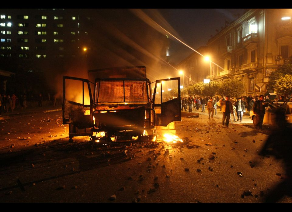 Egyptian demonstrators shout slogans next to a burning riot police vehicle in Cairo.