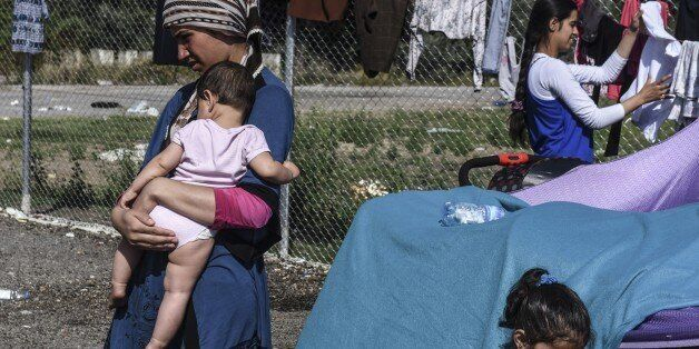 A refugee woman carries her baby at a makeshift refugee camp on the Serbian side of the border with Hungary near the town of