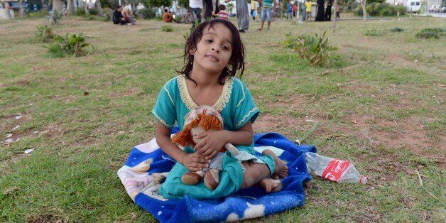 A Syrian girl sits with a doll on September 17, 2015 at a park where around 1000 Syrians migrants are gathering in the Morocc