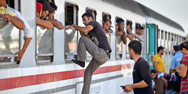 BELI MANASTIR, CROATIA - SEPTEMBER 18:  Migrants climb through windows to board trains at the train station in Beli Manastir,