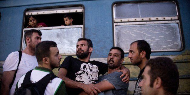 A man carries a disabled man as migrants and refugees queue to board the train heading to Serbia near the town of Gevgelija a