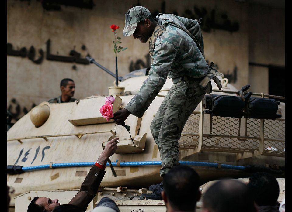 CAIRO, EGYPT - JANUARY 30:  An Egyptian Army soldier is a handed a flower by an anti-government protesters in Tahrir Square J