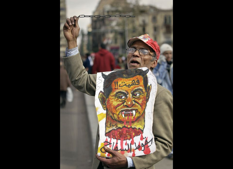 """An anti-government protester swings a metal chain and holds a poster representing Egyptian President Hosni Mubarak saying """"I"""