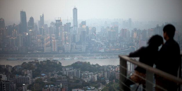 In this Tuesday April 3, 2012 photo, a couple observe the city skyline at a viewpoint in southwestern China's Chongqing city.