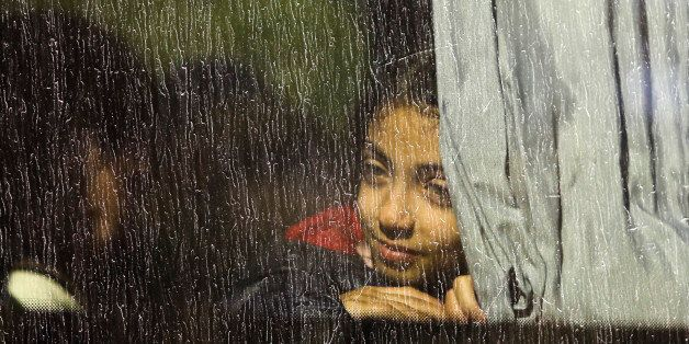 A girl looks out of a window as she sits in a bus which will transport migrants and refugees to a camp, after they were regis