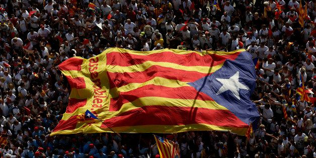 "People carry a giant ""estelada"" flag, a symbol of Catalonian pro-independence, during a demonstration calling for the ind"