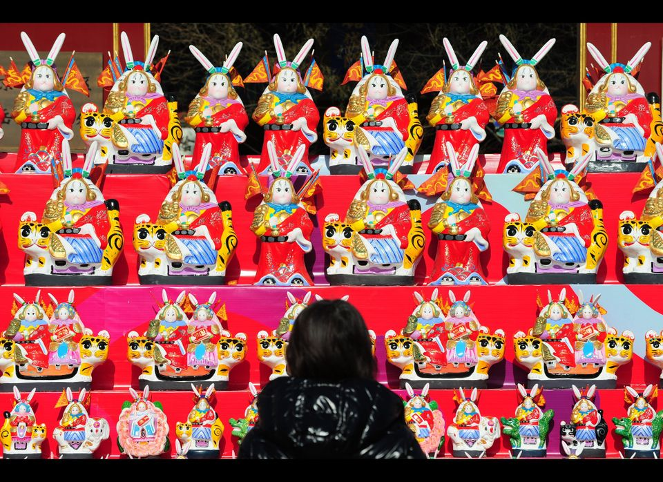 "A woman views a display featuring mythical Beijing folk icon ""Lord Rabbit"" figurines."