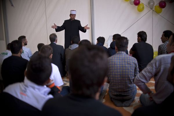 A Macedonian Imam delivers a speech to migrants and refugees, to mark the Eid-al-Adha festival, at a registration camp near G