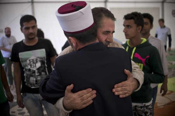 A migrant greets a Macedonian Imam during a prayer to mark the Eid-al-Adha festival at a registration camp near Gevgelija, cl