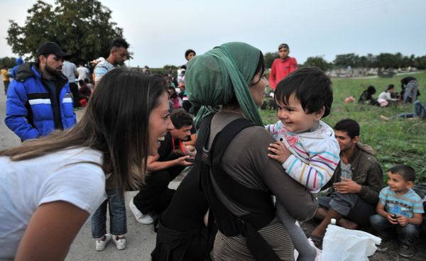 A woman speaks with a child in the Serbian-Croatian border village of Bapska, as migrants and refugees wait for a bus to the