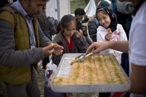 """Volunteers give migrants and refugees """"baklava,"""" a traditional sweet, as they mark the Eid-al-Adha festival at a registration"""