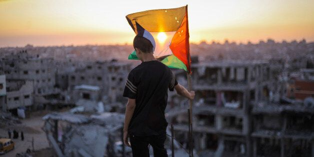GAZA, PALESTINE - 2014/09/19: A Palestinian child raises the flag of Palestine over the rubble of his ruined home, because of